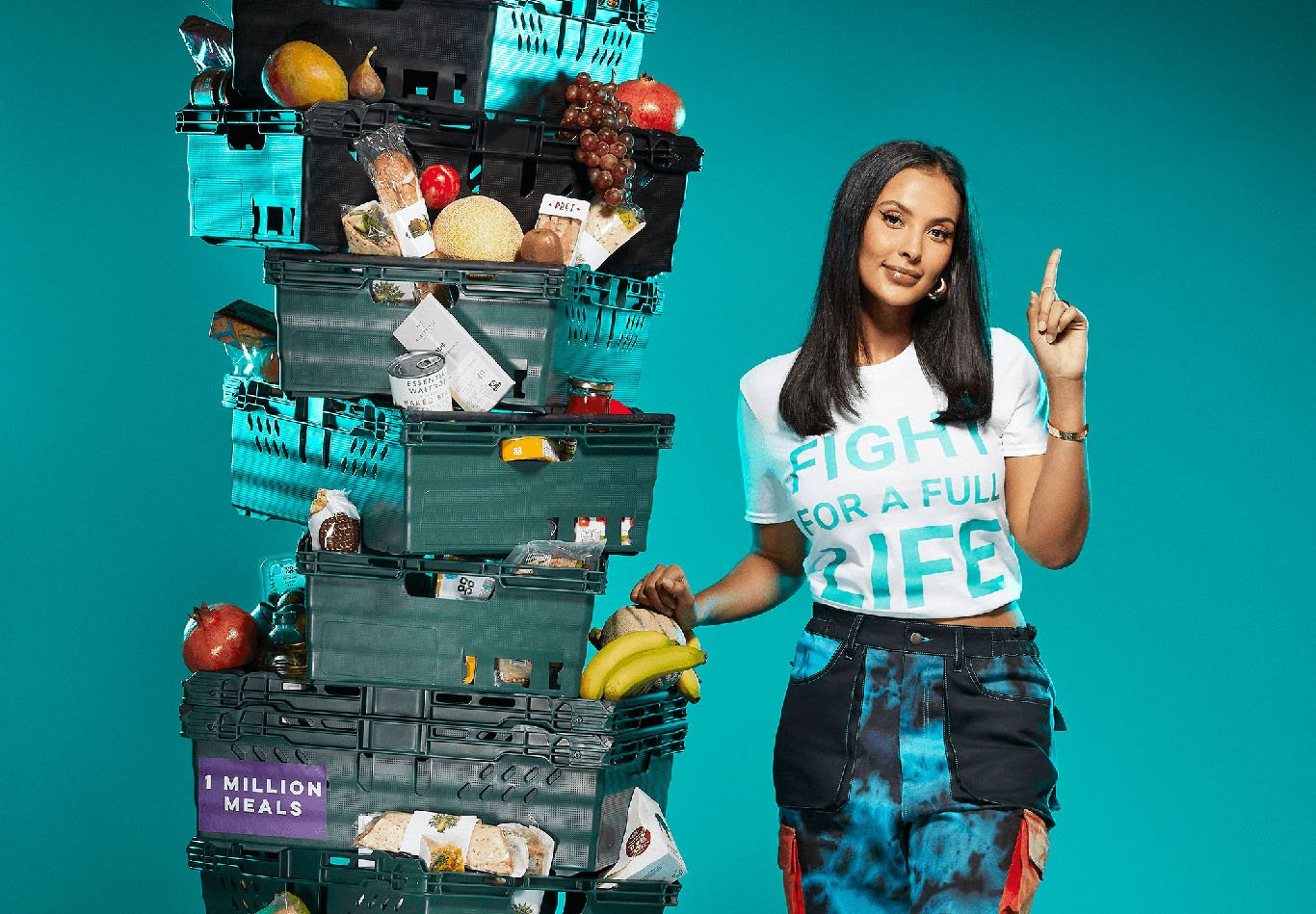 Maya Jama stands next to stacked baskets of food produce for Deliveroo's new campaign to donate one million meals to people in need